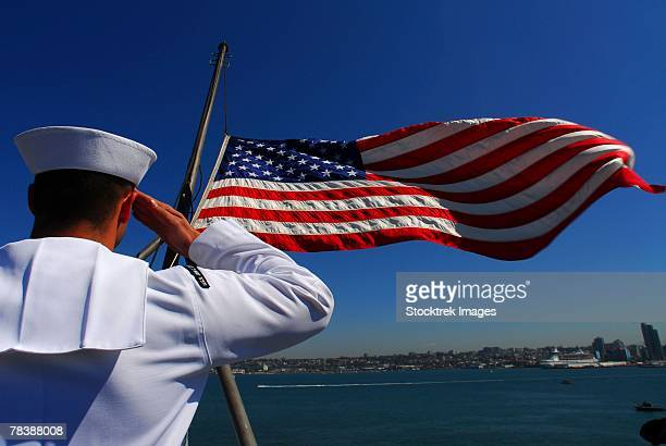 airman salutes the american flag. - sailor stock pictures, royalty-free photos & images
