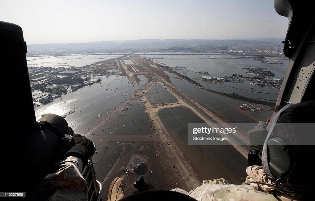 Airmen fly over the Sendai Airport in Japan to survey the tsunami aftermath. : Stock Photo