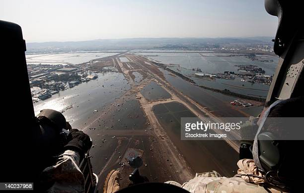 Airmen fly over the Sendai Airport in Japan to survey the tsunami aftermath.