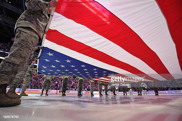 Airmen from WrightPatterson Air Force base hold the American flag during the National Anthem prior to the military appreciation game between the...