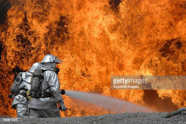 airmen neutralize a fire. - fire protection suit stock photos and pictures