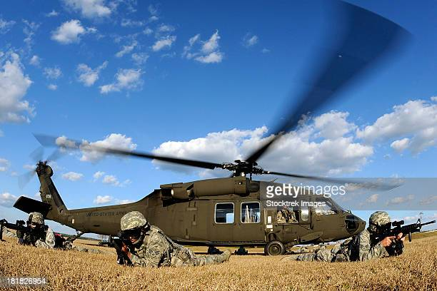 Airmen provide security in front of a UH-60 Black Hawk.