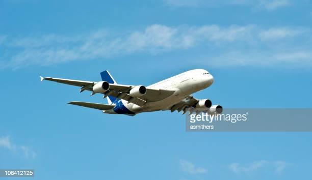 Airplane A380 flying through blue skies