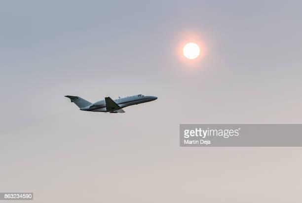 airplane against red sun - 自家用飛行機 ストックフォトと画像