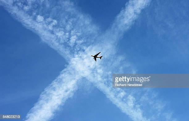 airplane and vapor trails - letter x stock pictures, royalty-free photos & images