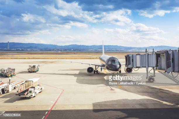 airplane at airport runway against sky - passenger boarding bridge stock pictures, royalty-free photos & images