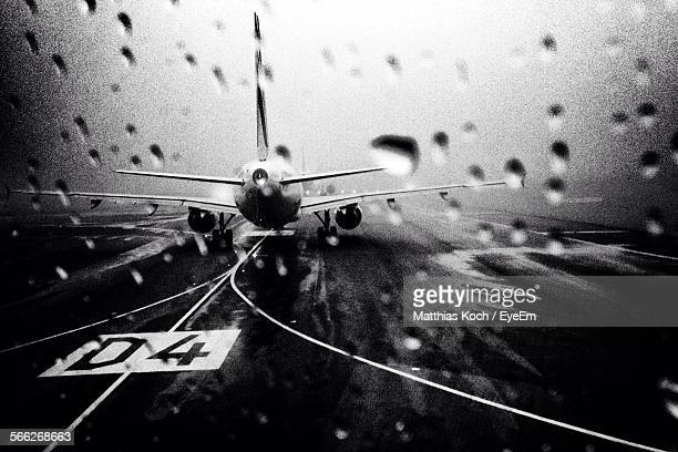 Airplane At Airport Seen Through Wet Glass