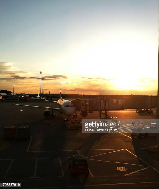 airplane at sunset - passenger boarding bridge stock pictures, royalty-free photos & images