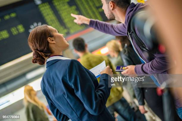 Airplane attendant helping traveler at timetables