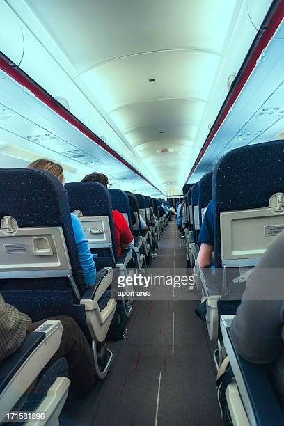 Airplane cabin aisle with rear view of passengers