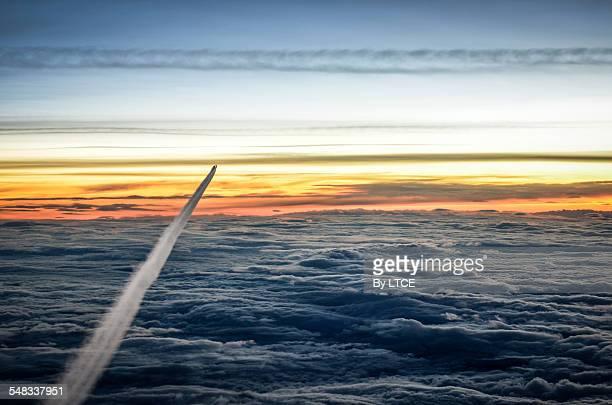 airplane contrails in flight at sunrise - carbon dioxide bildbanksfoton och bilder