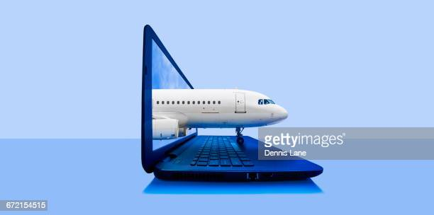 Airplane emerging from laptop screen