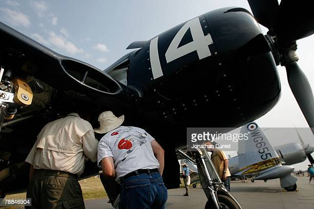 Airplane enthusiasts look into the wheel well of a post World War IIera F6F Bearcat fighter during the Experimental Aircraft Association's 2007...