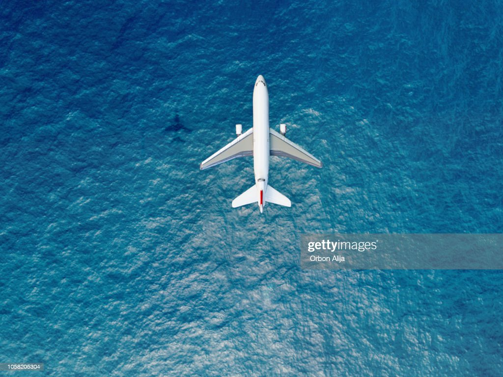 Airplane flies over a sea : Stock Photo