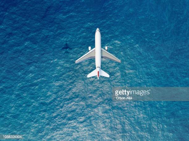 airplane flies over a sea - aeroplane stock photos and pictures