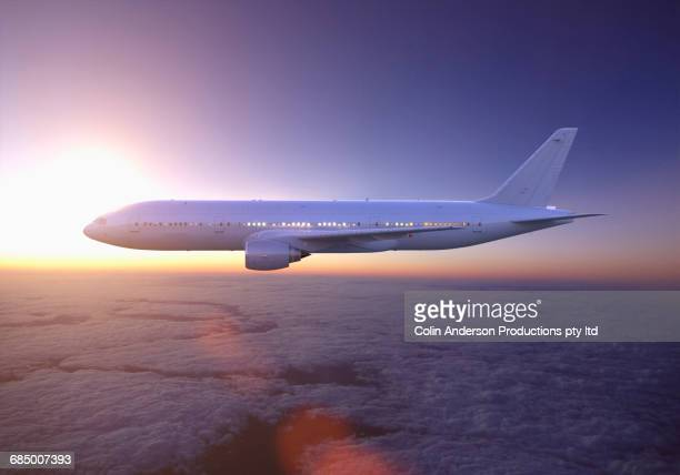 Airplane flying above clouds at sunset