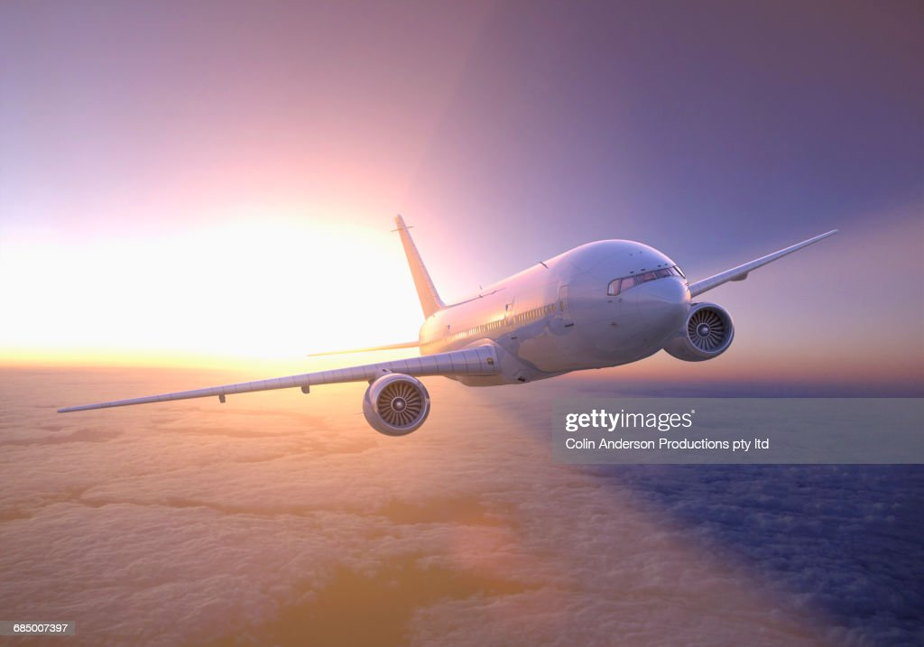 Airplane flying above clouds at sunset : Stock Photo