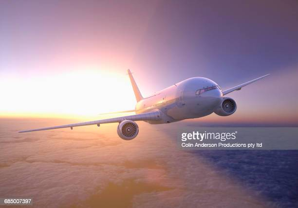 airplane flying above clouds at sunset - aeroplane stock photos and pictures