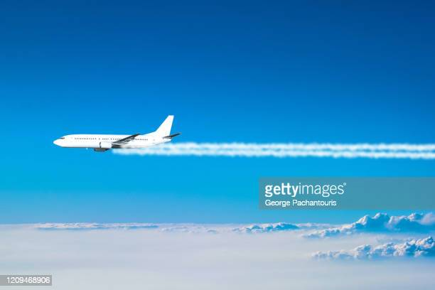 airplane flying above the clouds leaving a smoke trail - greenhouse gas stock pictures, royalty-free photos & images