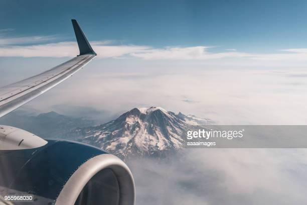 airplane flying across mt.rainier over clouds - aircraft wing stock pictures, royalty-free photos & images