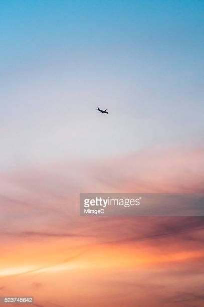 Airplane Flying Against Colorful Sunset Sky