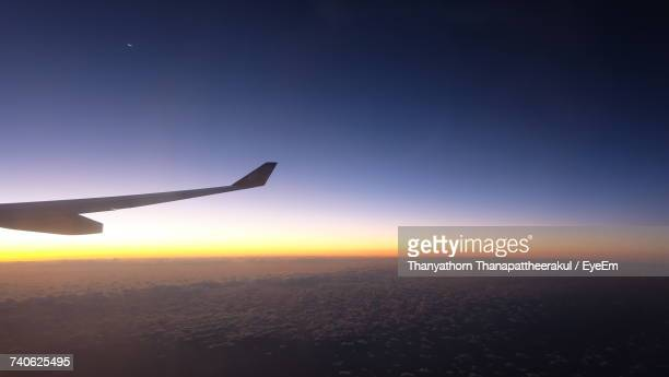 airplane flying in sky at sunset - narita stock photos and pictures
