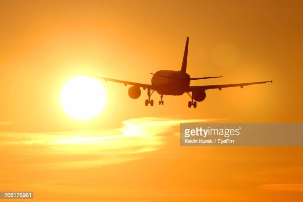 Airplane Flying In Sky During Sunset