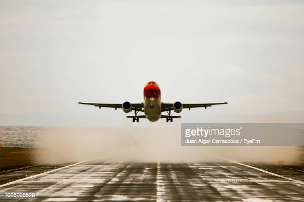 airplane flying in sky - landing gear stock photos and pictures