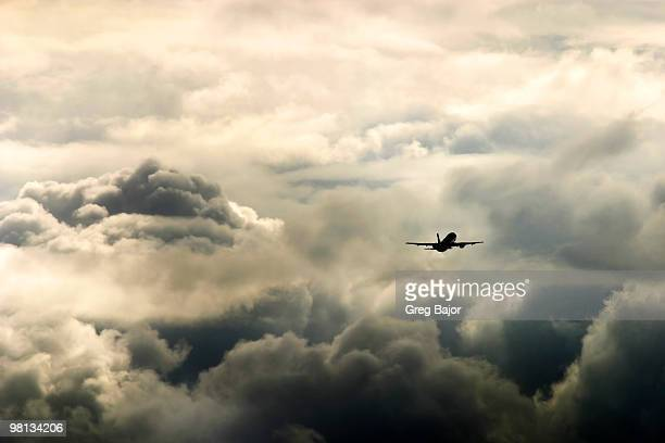 airplane flying in stormy weather - greg bajor stock pictures, royalty-free photos & images