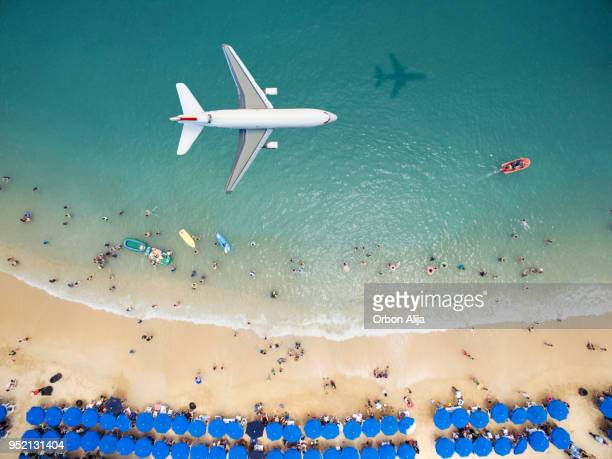 airplane flying over a crowded beach - aeroplane stock pictures, royalty-free photos & images