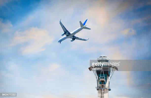 Airplane flying over air traffic control tower