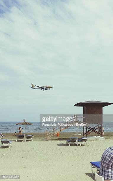 Airplane Flying Over Beach With Horizon In Background