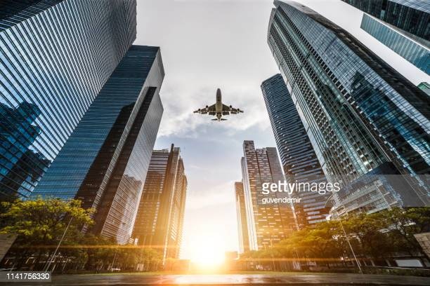airplane flying over central business district in singapore - singapore cbd stock pictures, royalty-free photos & images