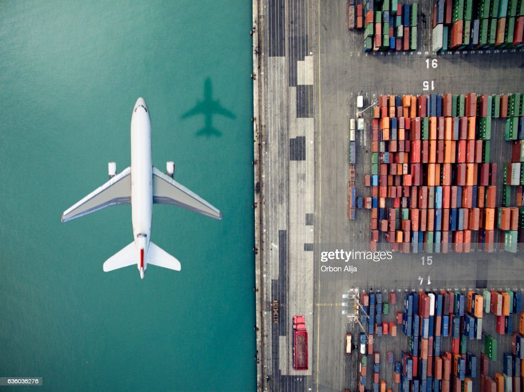 Airplane flying over container port : Stock Photo