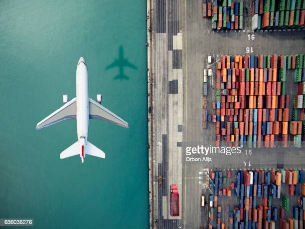 airplane flying over container port - transporte fotografías e imágenes de stock