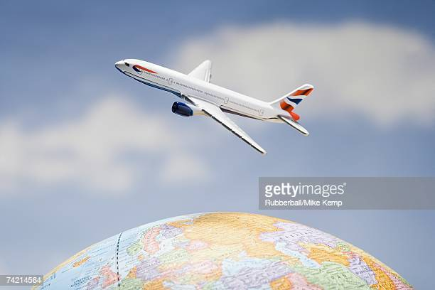 Airplane flying over globe with blue sky
