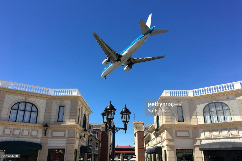 Airplane Flying over McArthurGlen Designer Outlets : Stock-Foto
