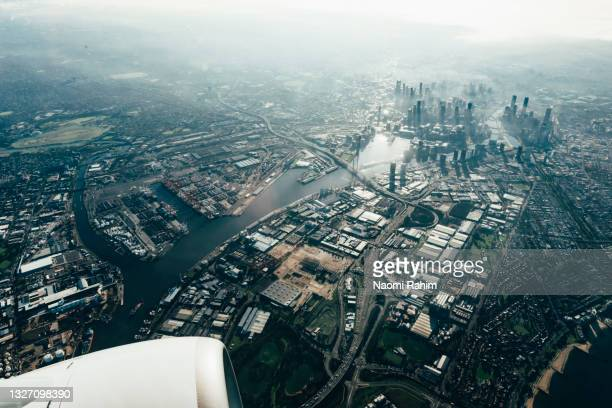 airplane flying over melbourne city skyline, australia - docklands stadium melbourne stock pictures, royalty-free photos & images