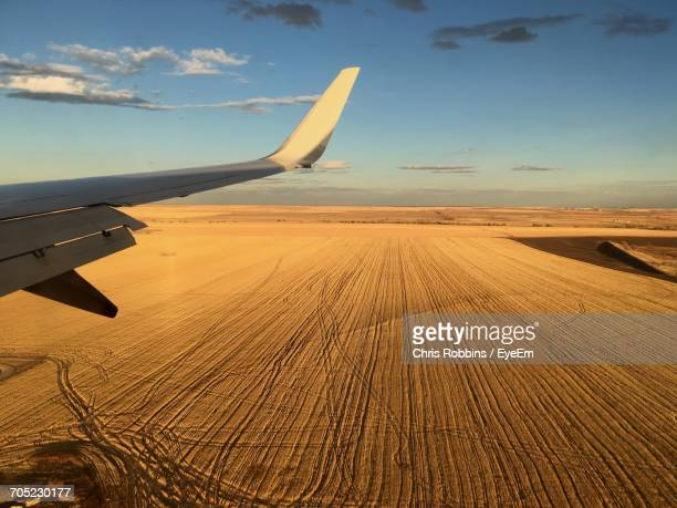 Airplane Flying Over Sand Dune In Desert Against Sky