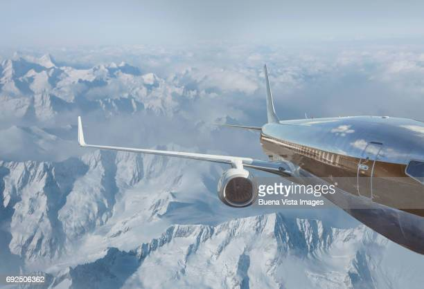 Airplane flying over snowy mountains
