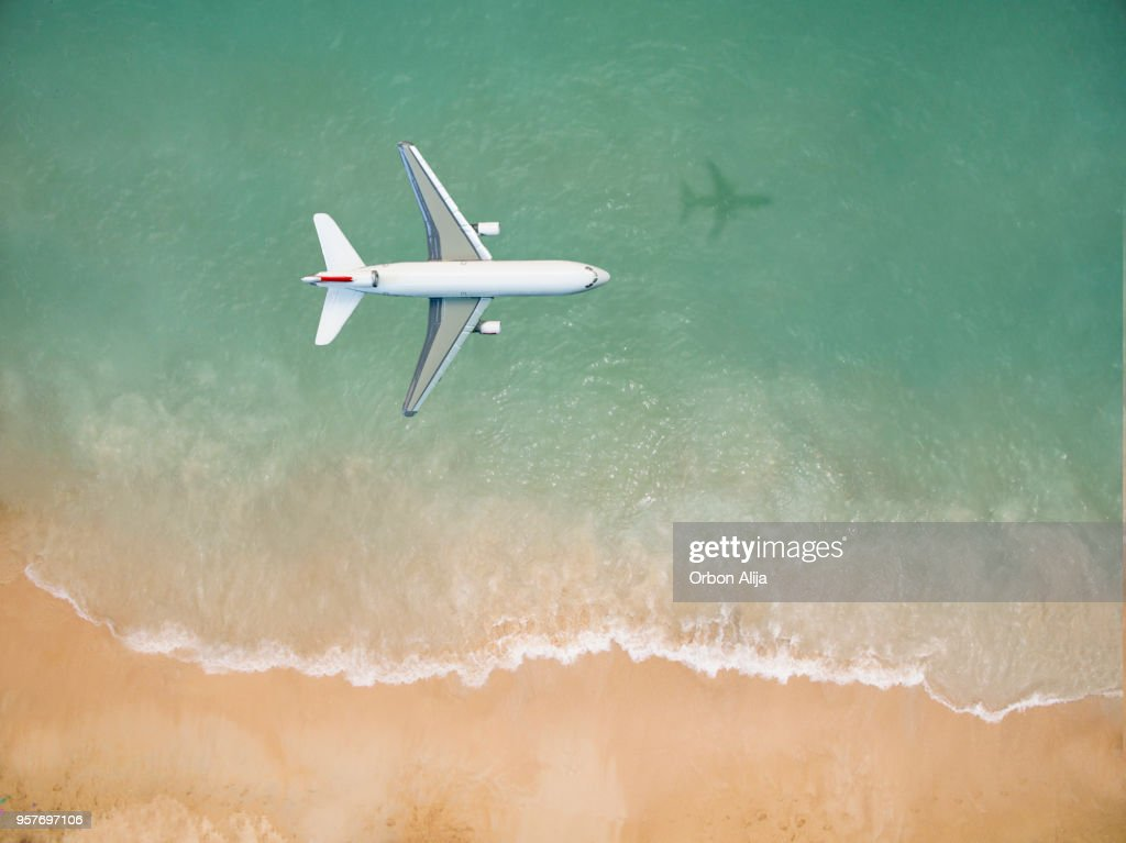 Airplane flying over the beach : Stock Photo