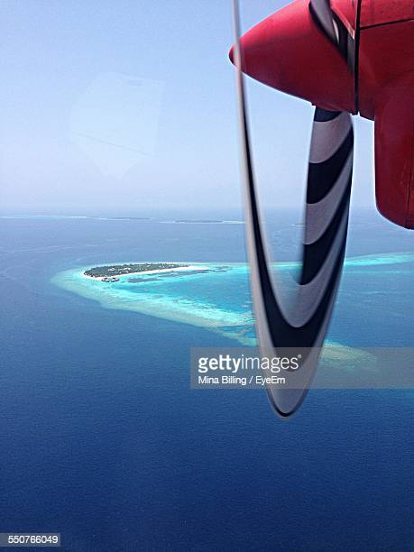 Airplane Flying Over Tropical Island