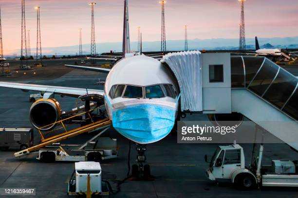 airplane in a medical mask. air travel crisis concept - coronavirus airport stock pictures, royalty-free photos & images