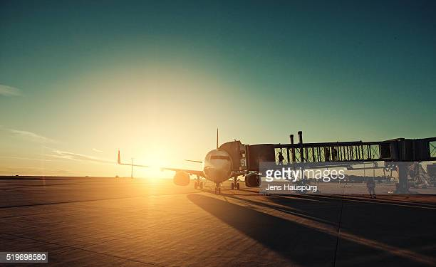airplane in airport runway during sunset - passenger boarding bridge stock pictures, royalty-free photos & images