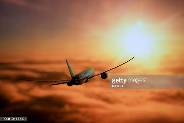 Airplane in flight at sunset, rear view
