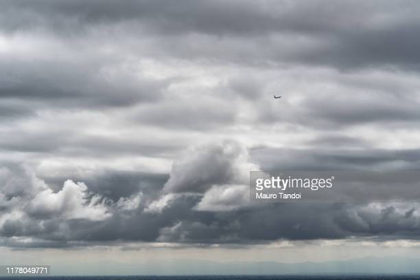airplane in the clouds - mauro tandoi stock pictures, royalty-free photos & images