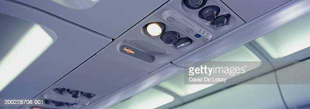 Airplane interior, close-up of overhead locker, vents and lights