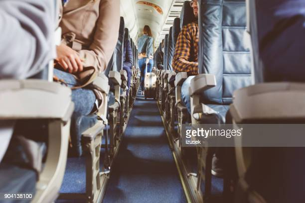 airplane interior with people sitting on seats - vehicle interior stock pictures, royalty-free photos & images