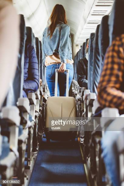 Airplane interior with woman carrying suitcase