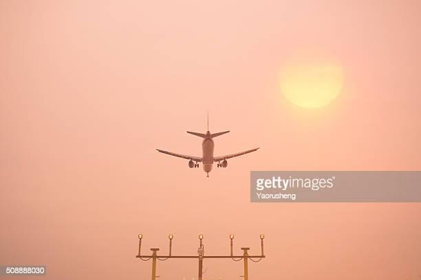 Airplane landing at Shanghai Hongqiao Airport. Runway lights in the foreground.